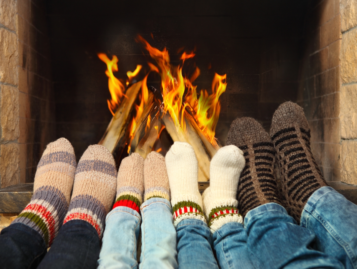 Feet with colourful socks sitting in front of a wood burning stove